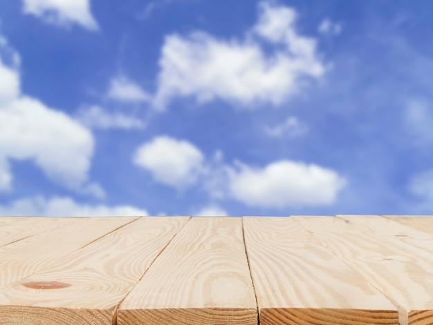 Mesa de madeira na frente do resumo borrado de fundo de céu azul.