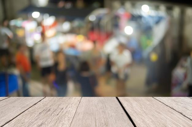 Mesa de madeira na frente turva noite mercado resumo, apresentação e modelo conceito