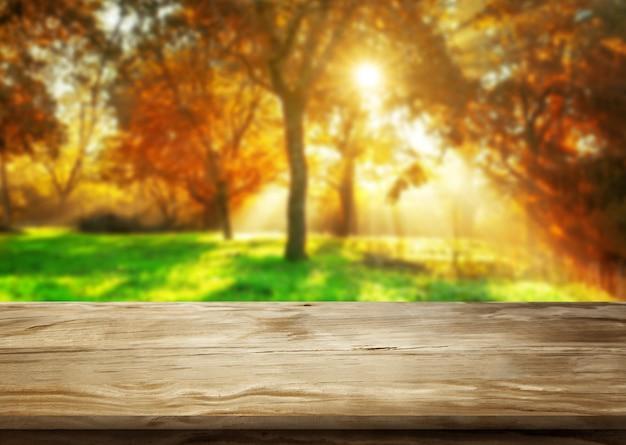 Mesa de madeira na paisagem de outono com espaço vazio da cópia para maquete de exposição do produto.