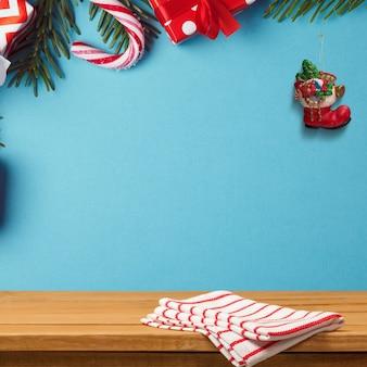 Mesa de madeira na parede azul decorada com enfeites de natal