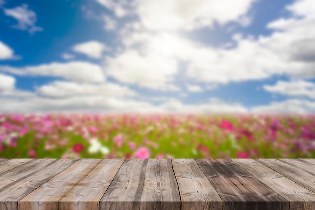 Mesa de madeira no borrão azul céu e cosmos flor fundo