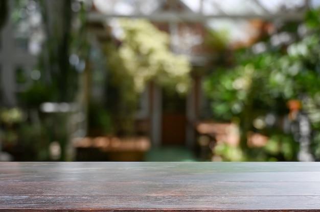 Mesa de madeira no fundo do jardim com mesa vazia.