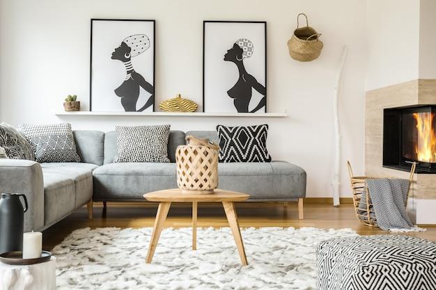 Mesa de madeira no tapete no interior da sala de estar africana com almofadas estampadas no sofá cinza