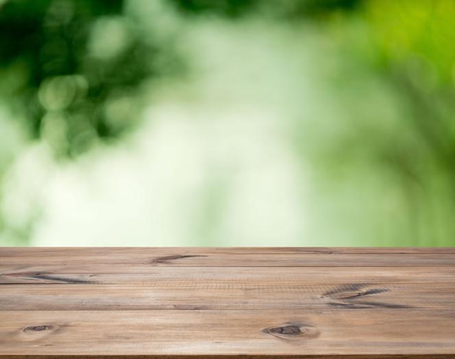 Mesa de madeira para design de decoração de interiores ou exibição de publicidade sobre fundo verde bokeh
