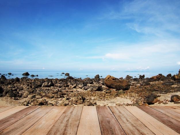 Mesa de madeira para produtos de exibição com vista para a praia e céu azul