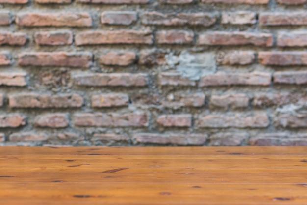 Mesa de madeira perto da parede de tijolos que desmorona