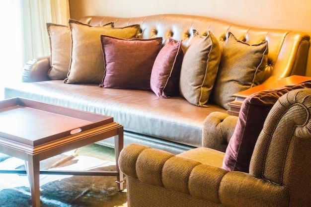 Mesa de madeira perto de sofás com almofadas