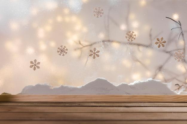 Mesa de madeira perto do banco de neve, galho de planta, flocos de neve e luzes de fada