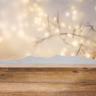 Mesa de madeira perto do banco de neve, ramo de planta e luzes de fada
