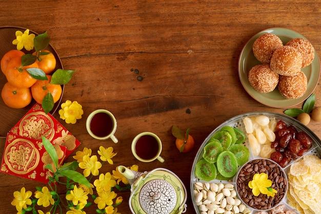 Mesa de madeira preparada para o ano novo chinês com xícaras de chá, caixa de frutas secas e nozes, bolinhos de arroz frito e cartões com a inscrição de votos de felicidades, vista de cima