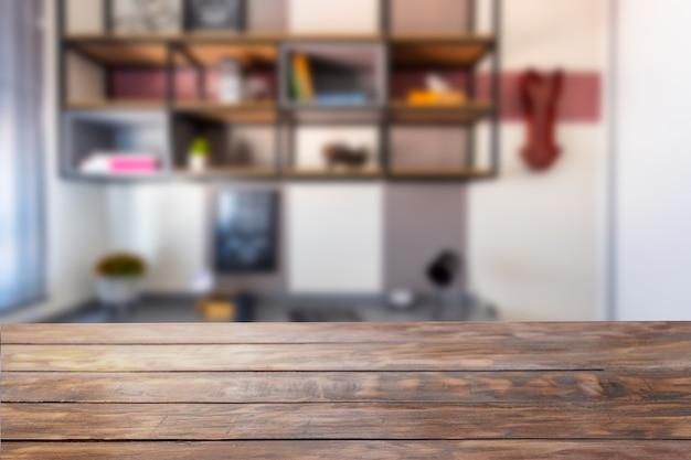 Mesa de madeira rústica em primeiro plano com um escritório com prateleiras suspensas no fundo desfocado.