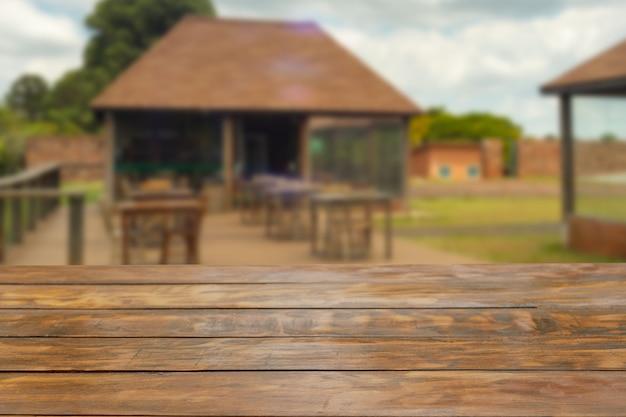 Mesa de madeira rústica em primeiro plano com uma cabana com mesas no fundo desfocado. Foto Premium