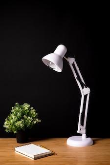 Mesa de madeira simples com lâmpada e notebook