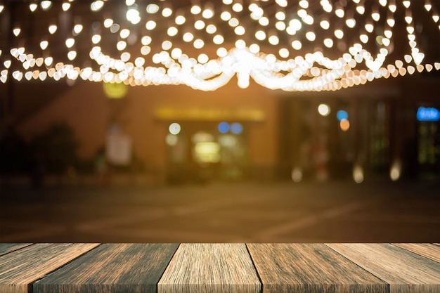 Mesa de madeira turva na frente turva mercado de rua à noite