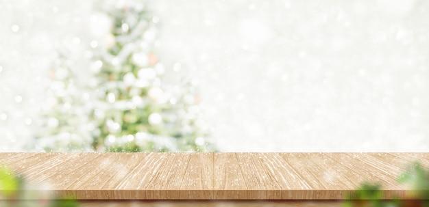 Mesa de madeira vazia com árvore de natal de borrão silenciado abstrata e fundo de queda de neve