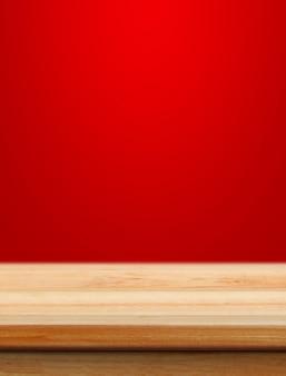 Mesa de madeira vazia com fundo vermelho de natal para colocação de produtos com borrão de fundo de papel de parede de natal