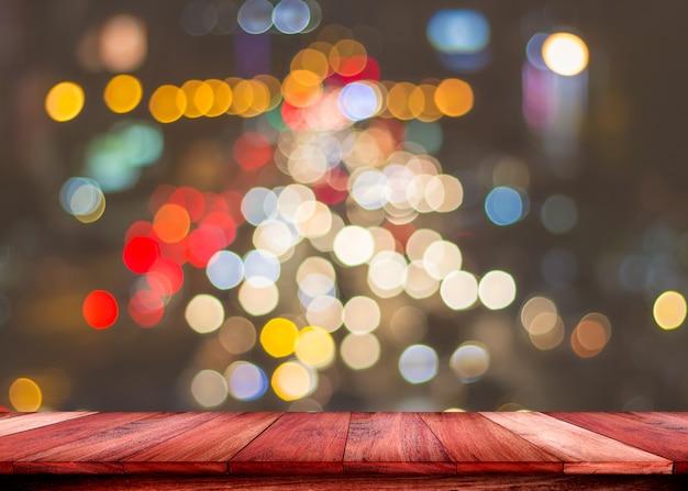 Mesa de madeira vazia com luzes desfocadas abstraem base de cor. para exibir ou montar seus produtos.