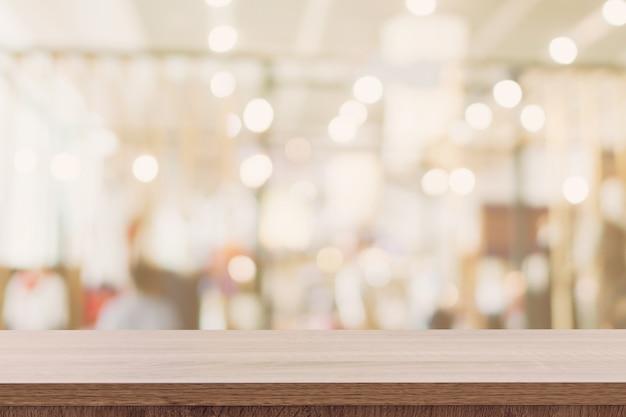 Mesa de madeira vazia com pessoas abstratas turva no café em fundo de restaurante.