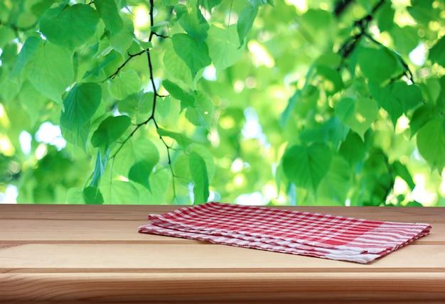 Mesa de madeira vazia com uma toalha sobre um fundo de folhas verdes