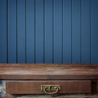 Mesa de madeira vazia contra uma parede das placas pintadas na cor azul.