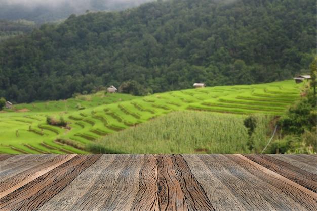Mesa de madeira vazia e campo de arroz turva e paisagem montanhosa na manhã.