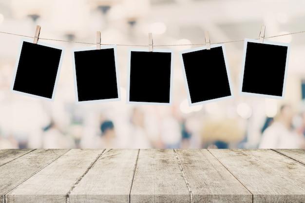 Mesa de madeira vazia e foto instantânea pendurado no fundo da imagem borrão de mont de exibição de pessoas