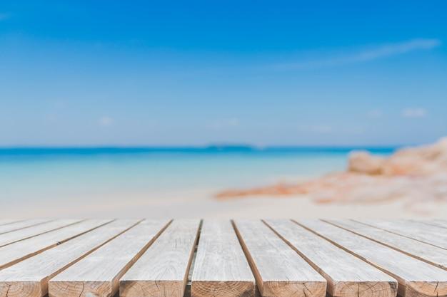 Mesa de madeira vazia e fundo de praia de verão borrado.