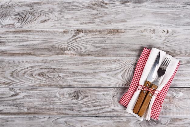 Mesa de madeira vazia e garfo e faca no guardanapo. jantar, almoço ou conceito de café da manhã.