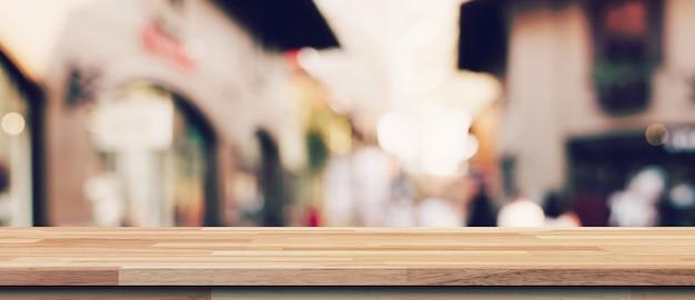 Mesa de madeira vazia e mesa de luz turva em shopping com fundo de bokeh. modelo de exibição do produto.
