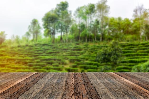 Mesa de madeira vazia e paisagem de plantação de chá turva na manhã.