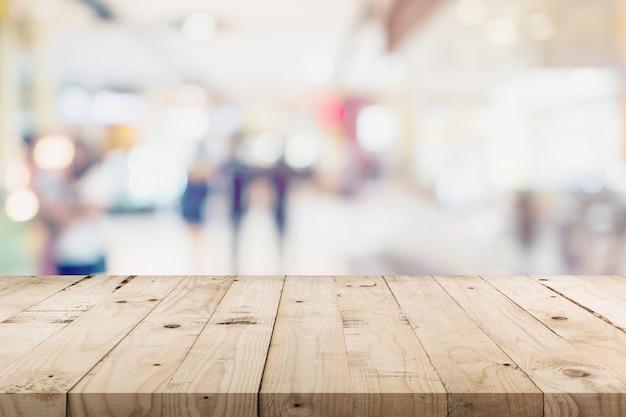 Mesa de madeira vazia e pessoas em compras em loja de departamento