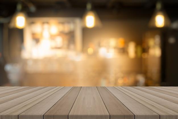 Mesa de madeira vazia em uma cafetaria em forma de borrão de fundo, para montar seus produtos