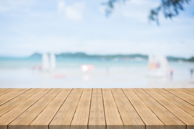 Mesa de madeira vazia na frente com fundo desfocado na praia e veleiro, espaço para montagem você produtos
