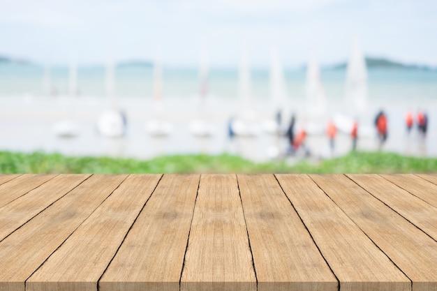 Mesa de madeira vazia na frente com fundo desfocado na praia e veleiro, espaço para montagem você produtos Foto Premium