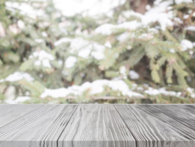 Mesa de madeira vazia na frente da árvore de natal com neve