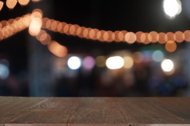 Mesa de madeira vazia na frente da luz noturna borrada abstrata