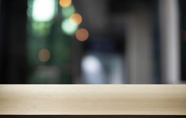 Mesa de madeira vazia na frente do abstrato desfocado
