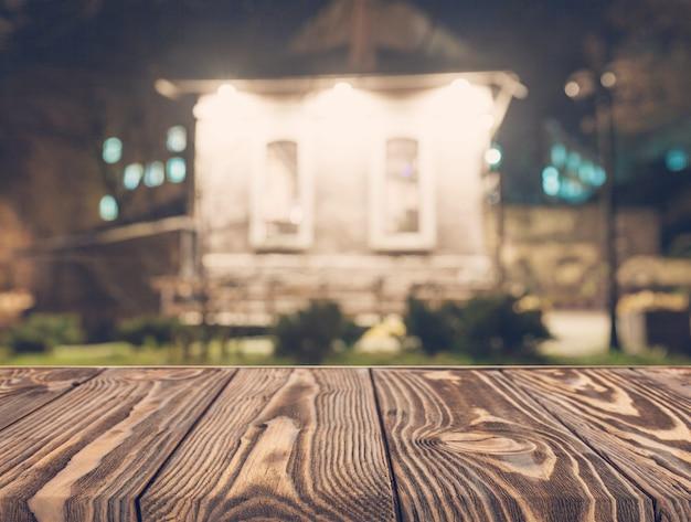 Mesa de madeira vazia na frente do pano de fundo da casa turva