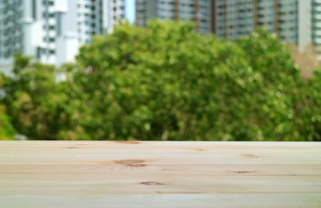 Mesa de madeira vazia na varanda com folhagem verde borrada e um edifício moderno ao fundo