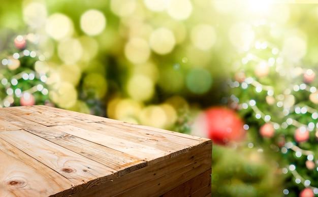 Mesa de madeira vazia no fundo da árvore de natal com luz bokeh