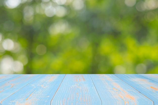 Mesa de madeira vazia no fundo natural verde no jardim ao ar livre