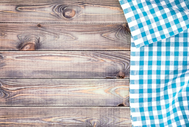 Mesa de madeira velha branca com toalha de mesa quadriculada azul, vista superior com espaço de cópia