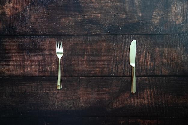 Mesa de madeira velha com garfo e faca à espera de um prato de falta de comida