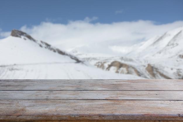 Mesa de madeira velha com pico de neve e fundo de céu azul