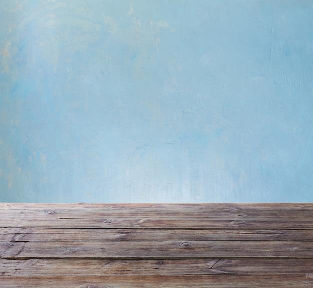 Mesa de madeira velha na parede azul do fundo