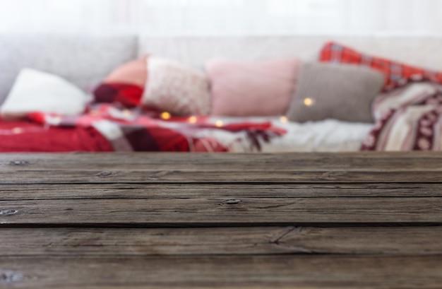Mesa de madeira velha no sofá de fundo com almofadas e mantas