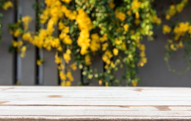 Mesa de madeira vintage com lindas flores amarelas e folhas verdes
