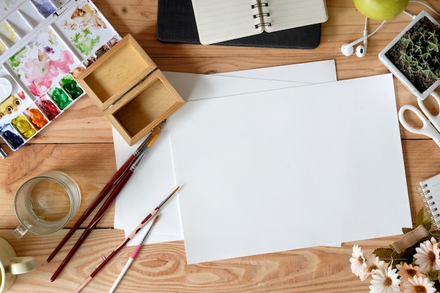 Mesa de madeira vista superior de um artista com lotes de papelaria objeto.