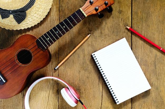 Mesa de madeira vista superior, há cadernos, lápis, chapéus, fones de ouvido e ukulele