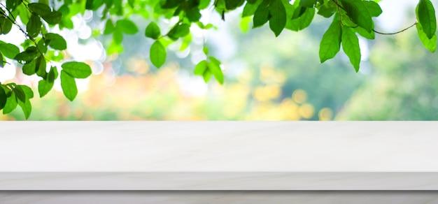 Mesa de mármore branca vazia sobre fundo de parque verde natureza borrão, montagem de exposição do produto
